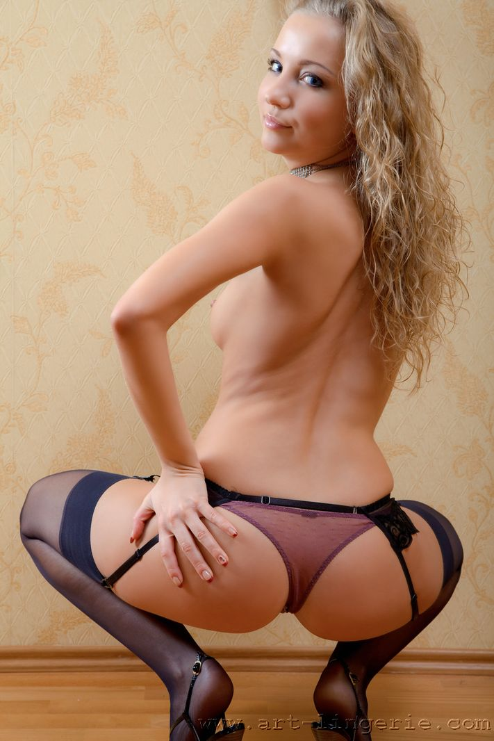 Curvacious blonde in purple lingerie and black stockings