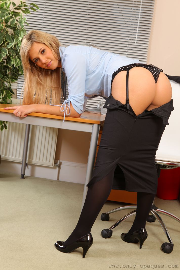 Sophia K entertains her colleagues by stripping out of her tight black skirt suit and showing off her sexy curves in just a paid or black stockings