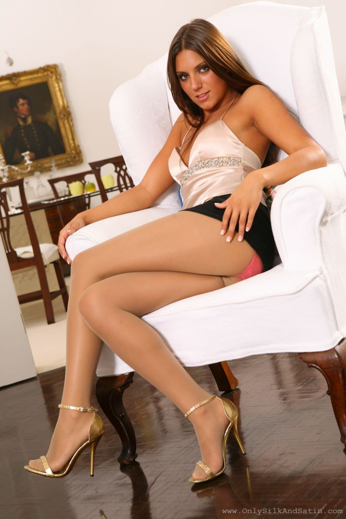 Charli posing in the living room with black miniskirt and sheer pantyhose